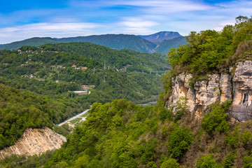 A huge rock with a green forest towers over the canyon with a road going uphill. Mountain valley on the way to Krasnaya Polyana from Adler, Sochi, Russia.