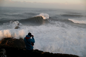 A man takes pictures of the waves before a surf session at Praia do Norte in Nazare