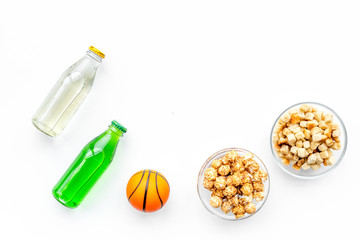 Snacks for watching sport matches and games on TV. Popcorn, rusks near drink and ball on white background top view copyspace
