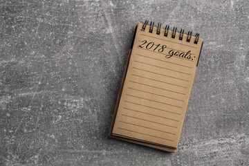 Circular notebook with brown sheets of paper on a concrete background with targets and goals for 2018