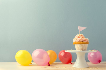 Sweet cupcake in composition with balloons