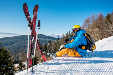 Professional skier sitting on top of the mountain near his skiing equipment relaxing enjoying beautiful snowy mountains view people living enjoyment recreation travelling riding lifestyle concept