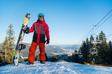 Full length portrait of male snowboarder, looking to the camera, resting after riding it the mountain winter ski resort copyspace ski-lift people lifestyle winter holidays vacation tourism travel