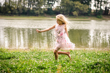 little lovely girl dancing in the grass by the river