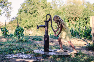 little child pumping water from the water well