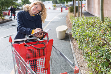 young woman in supermarket with empty shopping cart