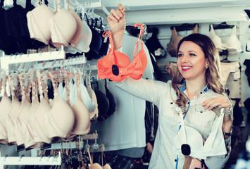 Female shopper examining bras in underwear shop