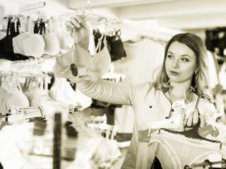 Smiling young woman customer choosing lingerie