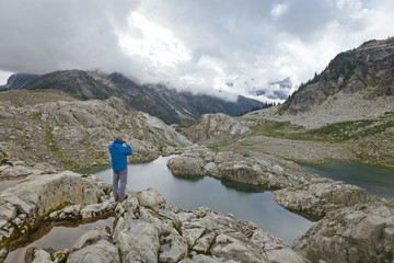 A mountaineer takes a photo of a mountain stream with his smart phone, Garibaldi Provincial Park