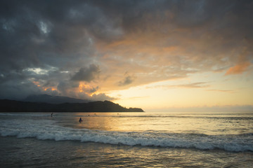 Surfers at Hanalei Bay at sunset