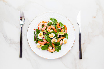 Fresh, healthy salad with shrimps, spinach and avocado on a marble table