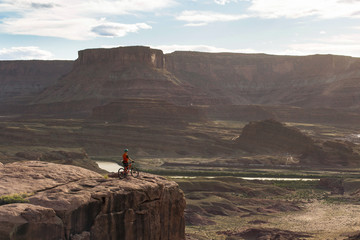 Side view of man with bike standing on mountain in Moab, Utah, USA