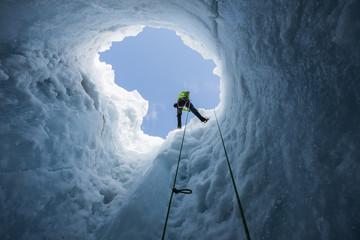 Man rappelling into moulin in Coleman Glacier, Mount Baker, Washington State, USA
