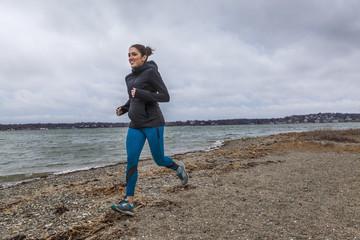 Woman jogging on beach, Hingham, Massachusetts, USA