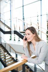 Business Frau hört eine Nachricht auf dem Smartphone