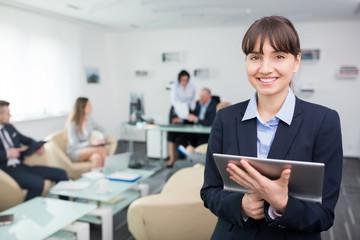 Junge Geschäftsfrau mit Tablet PC freut sich