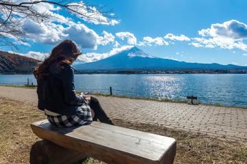 Wall Mural - Woman sitting on a bench at kawaguchiko lake, Japan. View of fuji mountains.