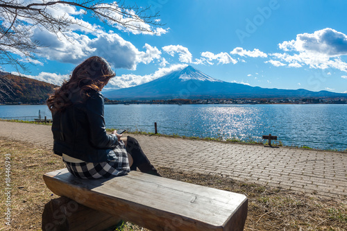 Wall mural Woman sitting on a bench at kawaguchiko lake, Japan. View of fuji mountains.