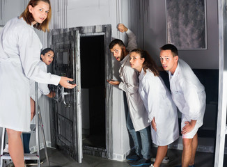Group of surprised adults wearing lab coats