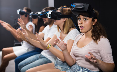 scared girl on virtual reality attraction sitting with another people