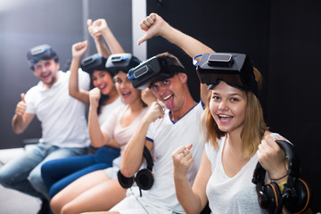 Group of cheerful friends are wearing virtual reality goggles