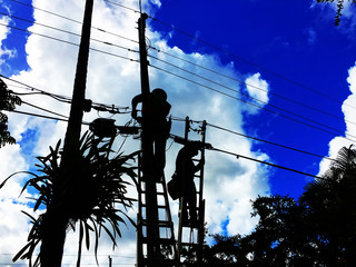 Silhouette of telecommunication workers on ladders pulling wires for new high speed fiber optics service in a residential neighborhood.