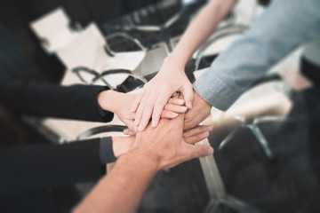 Business partners teamwork or friendship. Multi-ethnic diverse group of colleagues join hands together. Creative team, coworkers, or college students in project meeting at modern office.