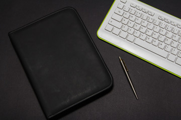 White keyboard on a black background with leather folder and pen. View from above.