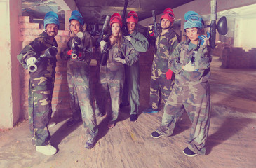 Portrait of red and blue teams who are ready for paintball