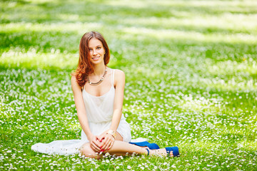 Beautiful young redhead woman on meadow with white flowers on warm summer day