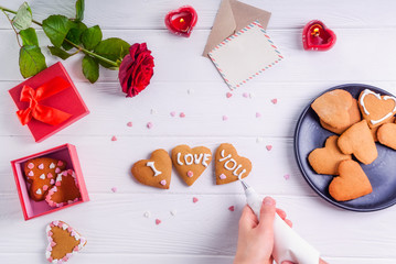 Top view female hands decorating homemade cookies in shape of heart as gift for lover on Valentine's day. White wooden table with greeting card, rose and decor. Selective focus. Copy space