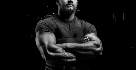 Huge powerlifter stands in front of the camera and strains his huge hands.