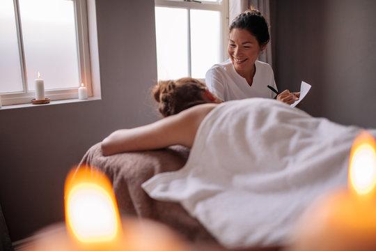 Female massage therapist talking to woman at wellness center