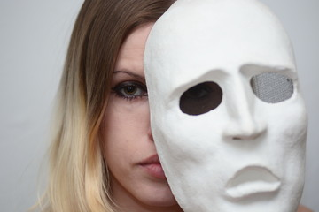 blonde girl holding a white theatrical mask