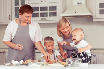 Grandmother, grandchildren and mother chefs in the domestic kitchen cooking a gingerbread cookies. Happy family concept