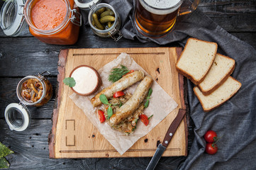rustic composition: chicken sausages on a grill with stewed cabbage, mushrooms and a glass of beer on a wooden background