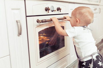 Cute funny blond kid cooking and preparing gingerbread cookies in domestic kitchen, sitting near oven and waiting for food