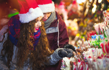 Couple at colorful Christmas market choosing things for buying