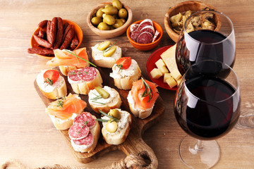Italian antipasti wine snacks set. Cheese variety, Mediterranean olives, pickles, salami, salmon, tomatoes, artichokes and wine in glasses. Spanish tapas