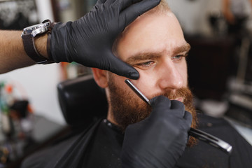 Close up male professional hairdresser serving client, shaving thick big beard straight razor. Ginger handsome young man with short hair getting trendy haircut in black cape. Light white barber shop.