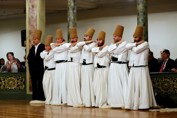 """Whirling dervishes perform a """"Sema"""" ritual during a ceremony, one of many marking the 744th anniversary of the death of Mevlana Jalaluddin Rumi, at Galata Mevlevi Temple in Istanbul"""