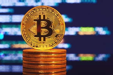 Golden bitcoin are stacked on a bright background of business graphs close-up. Bitcoin cryptocurrency. Anonymous