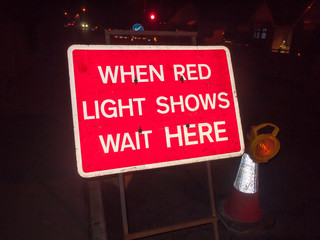 red construction sign at night road when red light shows wait here traffic lights