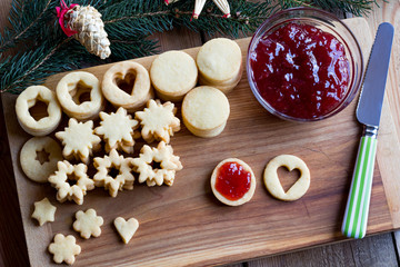 Preparation of traditional Linzer Christmas cookies - filling with jam