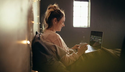 Woman on bed using laptop and having coffee.