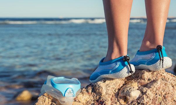 Female feet in aqua shoes near reefs and corals . Water sports equipment.
