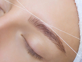 The make-up artist plucks her eyebrows with a thread close-up. Face care beauty treatments in the beauty salon.