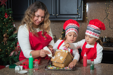 Happy Mom and twin girls in red making Christmas gingerbread house