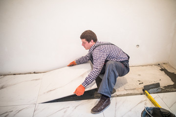 Laying Ceramic Tiles. Worker placing ceramic floor tile in position over adhesive. Spacers between ceramic floor tiles - close up