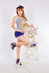 The girl in the style of Pin Up. Girl sailor in the style of Pin Up. The girl is holding the steering wheel from the box.